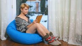 Het jonge vrouw ontspannen in kinderspel met tablet dichtbij het venster stock video