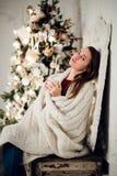 Het jonge vrouw ontspannen met een mok koffie aangezien zij omhoog in warme deken op oude ladenkast knuffelt Haar gesloten ogen e royalty-vrije stock afbeelding