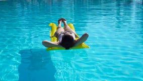 Het jonge vrouw ontspannen met luchtmatras in in openlucht zwembad stock video