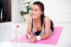 Het jonge vrouw ontspannen na training die thuis op het concepten gezonde levensstijl van de yogamat liggen, opleiding, dieet royalty-vrije stock foto