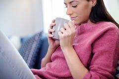 Het jonge vrouw ontspannen op bank met hete drank stock fotografie