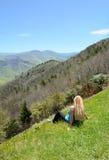 Het jonge vrouw ontspannen op de bovenkant van de berg Royalty-vrije Stock Foto