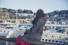 Het jonge vrouw ontspannen op de pijler Stock Afbeeldingen