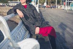 Het jonge vrouw ontspannen op de pijler Stock Foto
