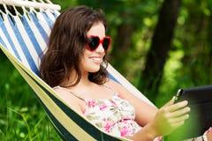 Het jonge vrouw ontspannen op hamock Stock Afbeelding