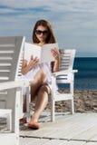 Het jonge vrouw ontspannen op het strand royalty-vrije stock afbeelding