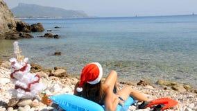 Het jonge vrouw ontspannen op het strand met Kerstmisboom stock footage