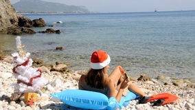 Het jonge vrouw ontspannen op het strand met Kerstmisboom stock videobeelden