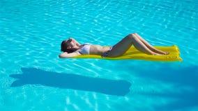 Het jonge vrouw ontspannen op luchtmatras in in openlucht zwembad stock footage
