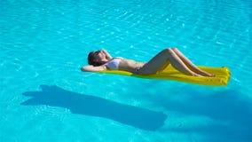 Het jonge vrouw ontspannen op luchtmatras in in openlucht zwembad stock video