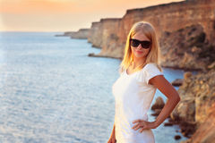 Het jonge Vrouw ontspannen Openlucht met blauwe Overzees en rotsenzonsondergang op achtergrond Stock Afbeelding