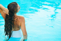 Het jonge vrouw ontspannen in pool. Achter mening Stock Afbeeldingen