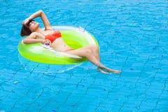 Het jonge vrouw ontspannen in zwembad royalty-vrije stock foto's
