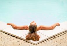 Het jonge vrouw ontspannen in zwembad Achter mening Stock Foto