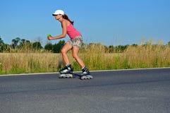 Het jonge vrouw rollerskating Stock Afbeelding