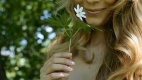 Het jonge vrouw ruiken brengt het aan zijn lippen witte bloem stock video