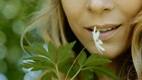 Het jonge vrouw ruiken brengt het aan zijn lippen witte bloem stock footage