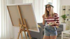 Het jonge vrouw schilderen op een canvas stock footage