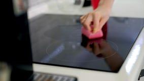 Het jonge vrouw schoonmaken met stofdoek bij keuken thuis stock footage