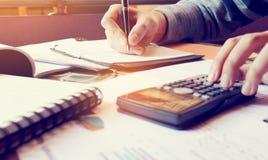 Het jonge vrouw schrijven maakt nota en het doen om financiën bij hom te berekenen Stock Fotografie