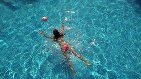Het jonge vrouw spelen met bal op zwembad stock footage