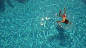 Het jonge vrouw spelen met bal op zwembad stock videobeelden