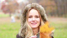 Het jonge vrouw spelen met blad stock video