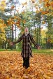 Het jonge vrouw spelen met de herfstbladeren Stock Foto's