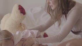 Het jonge vrouw spelen met een kleine zitting van het babymeisje op het bed De vreugden van moederschap Houdende van familie thui stock video