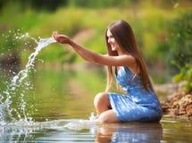 Het jonge vrouw spelen met water. Stock Foto's