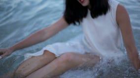 Het jonge vrouw spelen in water Mooie brunette op strand Griekenland stock videobeelden