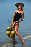 Het jonge vrouw stellen bij het tropische strand met kokosnoten Stock Afbeeldingen