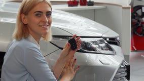 Het jonge vrouw stellen dichtbij haar nieuwe auto, die sleutels houden stock afbeelding