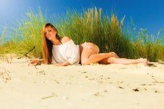 Het jonge vrouw stellen in grasrijk duin Stock Afbeelding