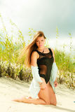 Het jonge vrouw stellen in grasrijk duin Stock Foto's