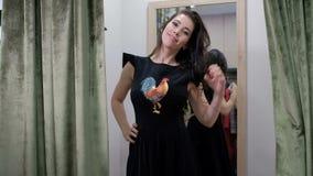 Het jonge vrouw stellen in kleding die zich in de opslag van de montageruimte bevinden stock footage