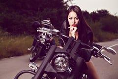 Het jonge vrouw stellen met een motorfiets stock afbeeldingen