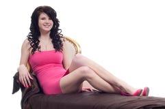 Het jonge vrouw stellen op een gouden stoel Stock Foto's