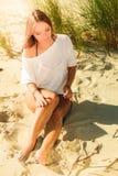 Het jonge vrouw stellen op grasrijk duin Stock Foto's