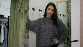 Het jonge vrouw stellen in sweater in de opslag van de montageruimte stock video