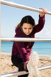 Het jonge vrouw strerching bij strand Royalty-vrije Stock Afbeelding