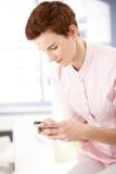 Het jonge vrouw texting op telefoon Stock Foto