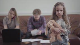 Het jonge vrouw typen op haar laptop die door celtelefoon en de gebaarde mens spreken die aan zijn tablet op de achtergrond werke stock video