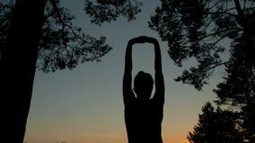 Het jonge vrouw uitrekken zich naar de hemel in het bos na zonsondergang Royalty-vrije Stock Foto's