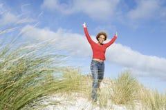 Het jonge vrouw uitrekken zich onder duinen Stock Foto