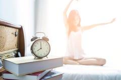 Het jonge Vrouw uitrekken zich op het bed na ontwaken Stock Afbeelding