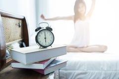 Het jonge Vrouw uitrekken zich op het bed na ontwaken in de ochtend Stock Foto's