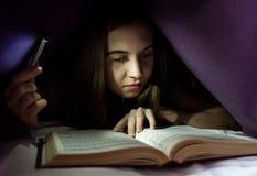 Het jonge vrouw verbergen in het kader van algemeen en enrapt lezings interessant boek bij nacht Meisjesverlichting met de telefo royalty-vrije stock afbeelding