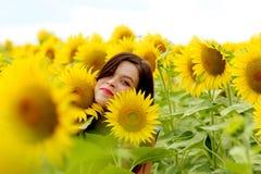 Het jonge vrouw verbergen in zonnebloemen stock afbeelding
