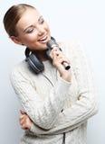 Het jonge vrouw zingen in microfoon met hoofdtelefoons in studio  stock foto